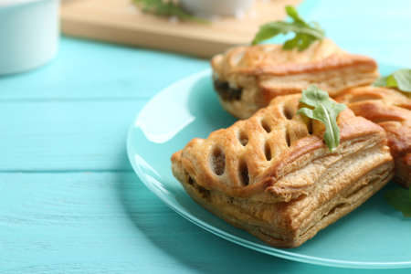 Fresh delicious puff pastry served on light blue wooden table, closeup