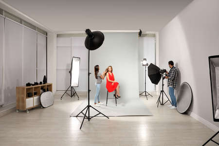 Professional photographer and assistant working with model in modern studio Stok Fotoğraf