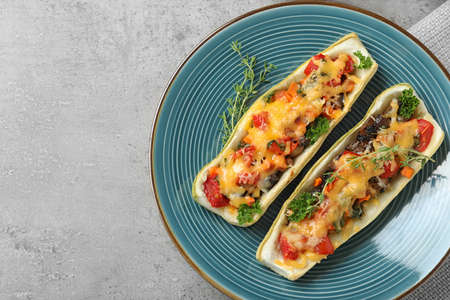 Plate of delicious stuffed zucchini on light grey table, top view. Space for text