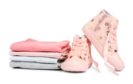Stylish child shoes and stack of clothes on white background