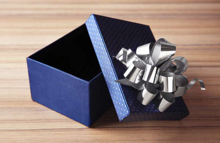 Open empty gift box with bow on wooden table