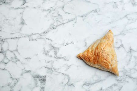 Fresh delicious puff pastry on white marble table, top view. Space for text