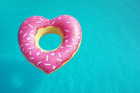 Heart shaped inflatable ring floating in swimming pool on sunny day, above view. Space for text