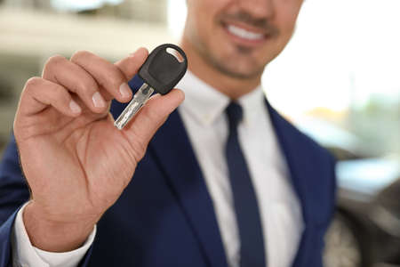 Young salesman with car key in modern dealership, focus on hand