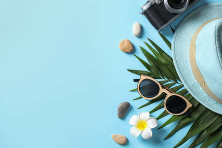 Flat lay composition with stylish beach accessories on light blue background, space for text