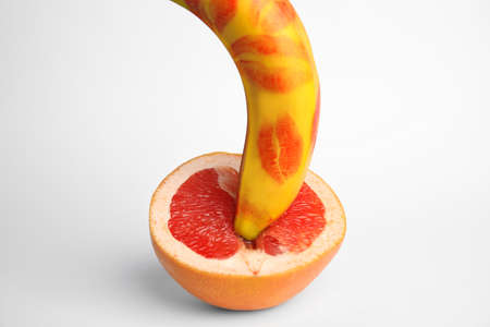 Fresh grapefruit and banana with red lipstick marks on white background. Sex concept