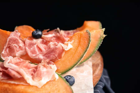 Wooden board with melon, prosciutto and blueberries on table against black background