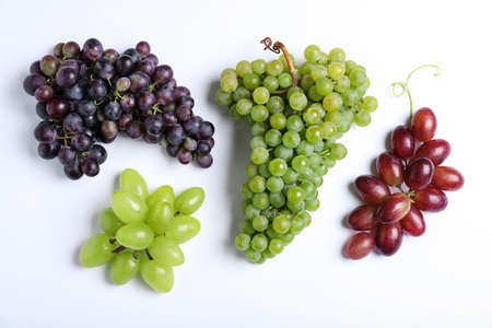 Different fresh ripe juicy grapes on white background, top view