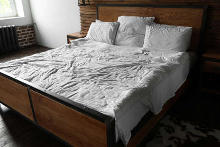 Comfortable bed with crumpled linen and pillows in stylish room interior 写真素材