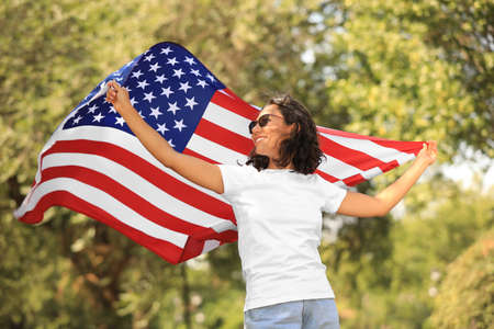 Happy young woman with American flag in park on sunny day