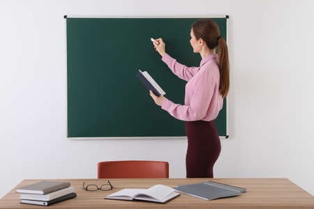 Portrait of young female teacher in classroom Imagens