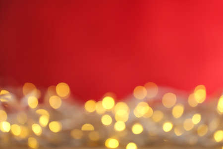 Blurred yellow Christmas lights against red background