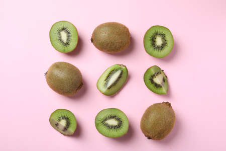 Top view of cut and whole fresh kiwis on pink background