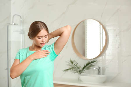 Young woman with sweat stain on her clothes in bathroom. Using deodorant 写真素材