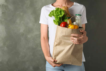 Woman holding shopping paper bag with different groceries against grey background. Space for text