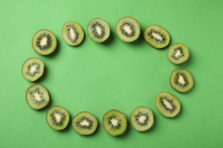 Frame made of fresh kiwis on green background, top view. Space for text