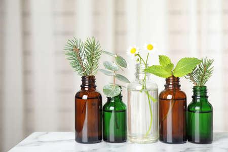 Glasflaschen mit verschiedenen ätherischen Ölen mit Pflanzen auf dem Tisch