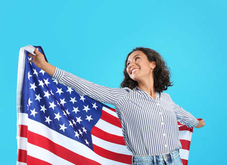 happy young woman with USA flag on blue background