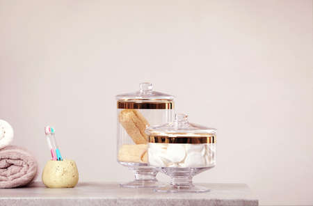 Composition of glass jar with cotton pads on table near light wall