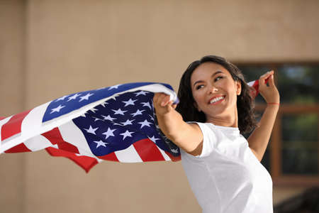 Happy young woman with American flag on sunny day Фото со стока