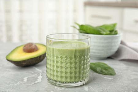Szklanka smacznego smoothie z awokado na jasnoszarym marmurowym stole