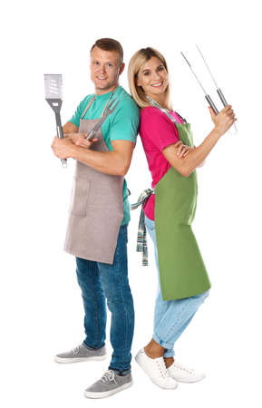 Happy couple with barbecue utensils on white background