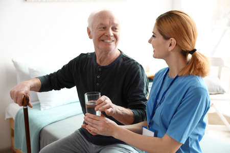 Infermiera che dà bicchiere d'acqua all'uomo anziano al chiuso. Assistenza medica Archivio Fotografico