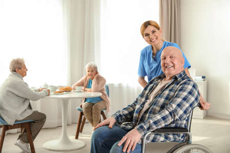 Nurse assisting elderly man in wheelchair at retirement home. Space for text Imagens
