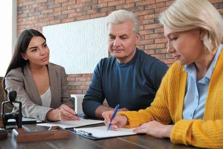 Notaire féminin travaillant avec un couple d'âge mûr au bureau