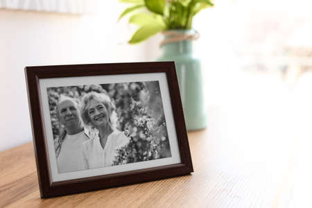 Portrait of senior couple in frame on table indoors. Space for text Stock fotó