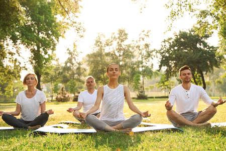 Gente practicando yoga en el parque por la mañana