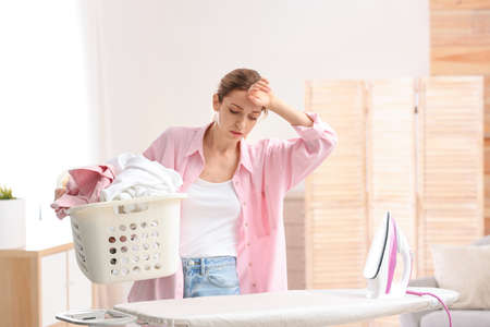 Young tired woman holding basket of clean laundry at ironing board indoors Standard-Bild - 129708605