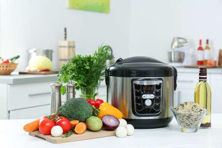 Cuisinière et produits multi modernes sur la table de cuisine