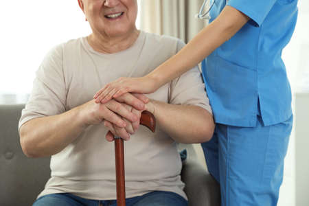 Nurse assisting elderly man with cane indoors, closeup