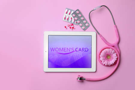 Tablet, flower, stethoscope and pills on pink background, flat lay. Gynecological care 写真素材