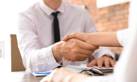 Geschäftspartner, die sich am Tisch die Hände schütteln, nachdem sie sich im Büro getroffen haben, Nahaufnahme