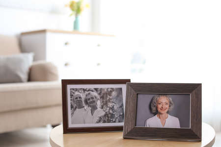 Portraits in stylish frames on table indoors Foto de archivo - 129524286