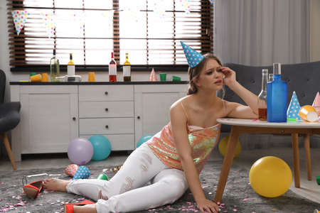 Young woman suffering from hangover in messy room after party