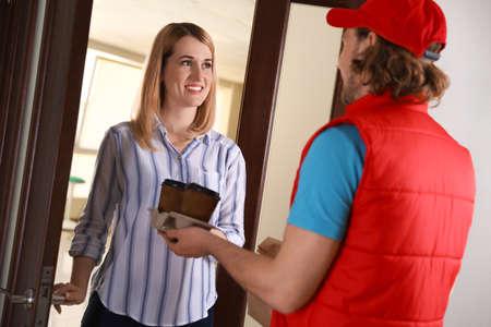 Femme recevant l'ordre du courrier à la porte. Service de livraison de nourriture