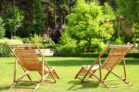 Wooden deck chairs in beautiful garden on sunny day Stock fotó