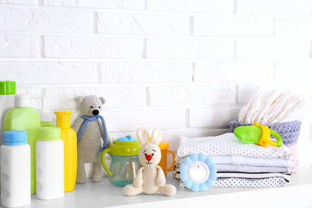 Baby accessories on shelf near white brick wall. Space for text