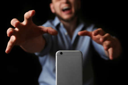 Emotional man reaching for smartphone on black background, closeup. Addiction concept