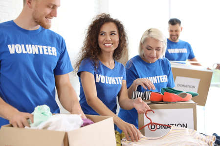 Team of volunteers collecting donations in boxes indoors
