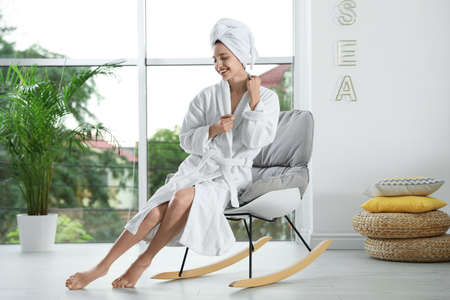 Pretty young woman with towel on head sitting in rocking chair near window indoors