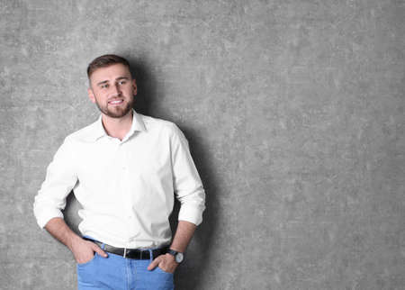 Portrait of handsome happy man on grey background, space for text Stock Photo