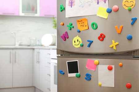 Sheets of paper, childs drawing and magnets on refrigerator door in kitchen. Space for text Imagens