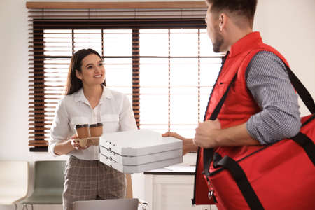 Courier giving order to young woman in office. Food delivery service