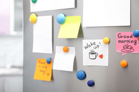Many notes and empty sheets with magnets on refrigerator door in kitchen. Space for text