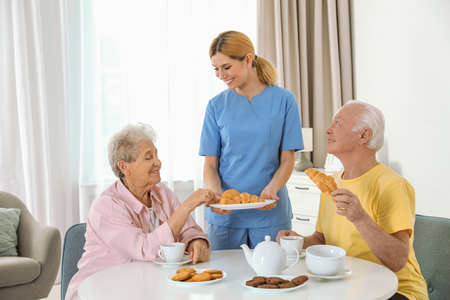 Nurse assisting while elderly people having breakfast at retirement home
