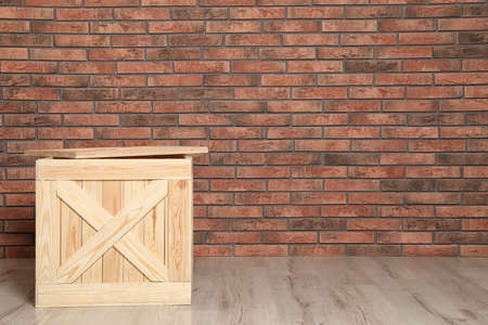 Wooden crate on floor at brick wall. Space for text Foto de archivo - 129526487